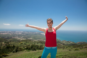 Fitness girl on top of rocks with arms wide open