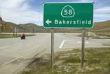 A motorcycle driving past a road sign pointing to Route 58 near Bakersfield CA