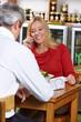 Frau telefoniert beim Essen im Restaurant