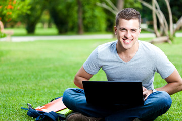 Young student using a laptop in the park