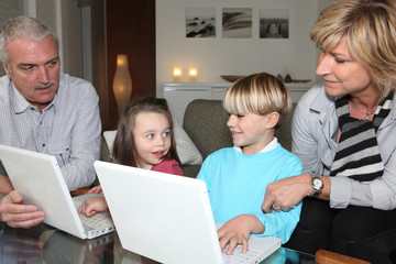 Grandparents with children and laptops