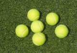SIx yellow tennis balls lays on green synthetic court grass poster