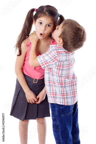 Little boy whispering something to girl