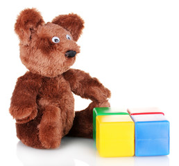 Sitting bear toy and color cubes isolated on white