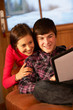 Teenage Couple Relaxing On Sofa With Tablet Computer