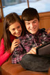 Teenage Couple Relaxing On Sofa With Laptop