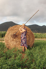 nonna contadina con rastrello e pagliaio