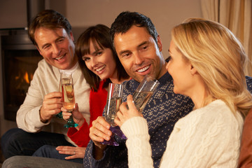 Group Of Middle Aged Couples Sitting On Sofa With Champagne
