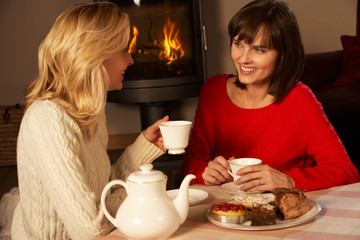 Two Middle Aged Women Enjoying Tea And Cake Together