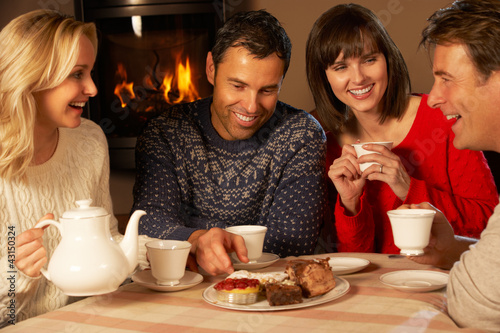 Group Of Middle Aged Couples Enjoying Tea And Cake Together