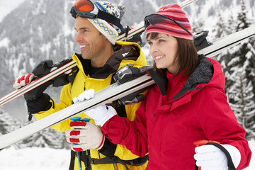Middle Aged Couple On Ski Holiday In Mountains
