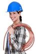 Female plumber holding pipe