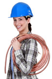 Female plumber holding pipe