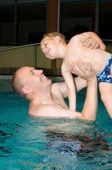 Kleinkind mit Vater im Hallenbad
