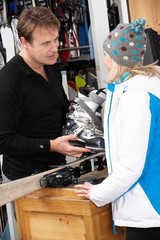 Sales Assistant Helping Advising Female Customer On Ski Boots In