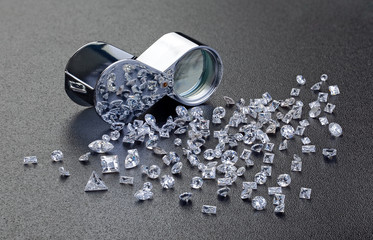 loose diamonds next to a 10x  magnifier glass
