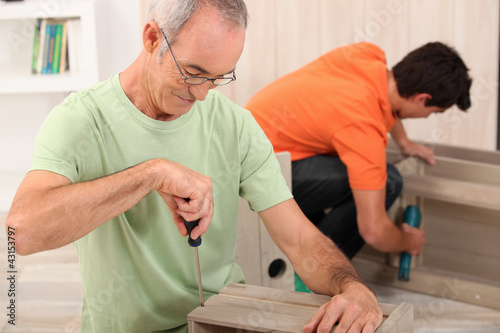 Father and son putting together flatpack furniture