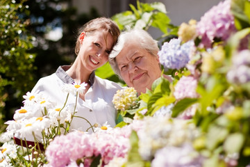 Altenpflegerin mit Seniorin im Garten