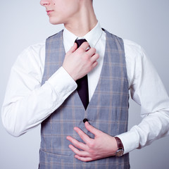 business man adjusting tie in gray waistcoat