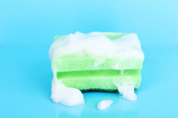 Sponge with foam of dishwashing liquid on blue background