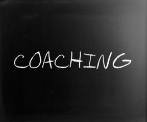 """Coaching"" handwritten with white chalk on a blackboard"