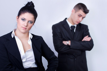 modern young business couple posing on gray background