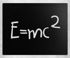 E=mc2 handwritten with white chalk on a blackboard