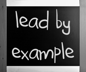 """""""Lead by example"""" handwritten with white chalk on a blackboard"""