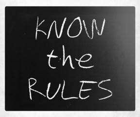 """Know the rules"" handwritten with white chalk on a blackboard"