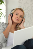 Blond woman listening to music through laptop