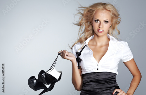 Beautiful woman after party holding shoes . Girl and shoes