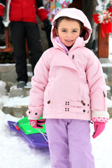 Little girl in snowsuit holding sled
