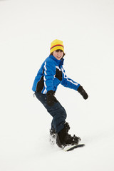 Young Boy Snowboarding Down Slope On Holiday In Mountain