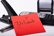 Büromaterial und eine rote Notiz mit dem Wort Urlaub