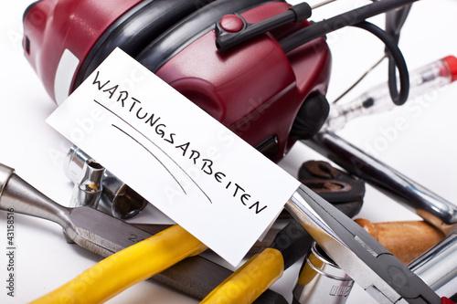 Notiz Wartungsarbeiten vor einer Sammlung von Werkzeug