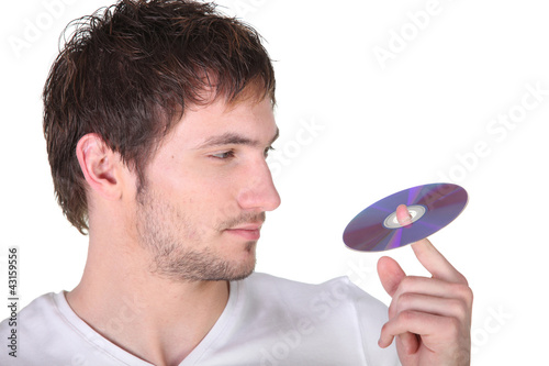 Young man spinning a digital recording disc on his finger