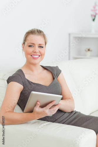 Woman smiling using a tablet pc