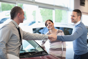 Car dealer shaking hand with a smiling man