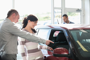 Car dealer pointing the interior of a car with a woman
