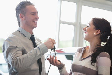 Laughing salesman giving keys to a woman