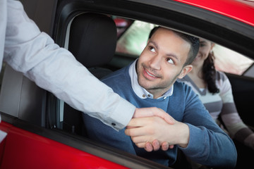 Man shaking the hand of a car dealer