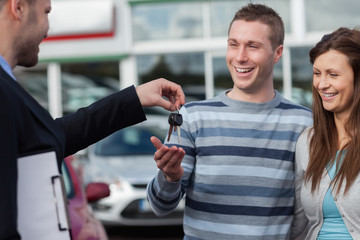 Couple receiving car keys by a dealer