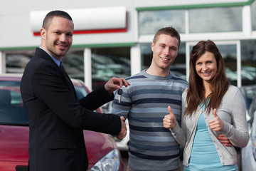 Dealer shaking hand of a man while giving him car keys