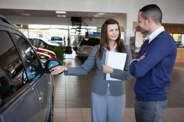 Businesswoman presenting a car to a client