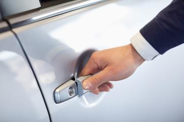 Close up of a man opening a car door