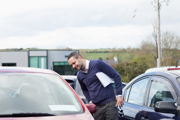 Man looking at a car while leaning