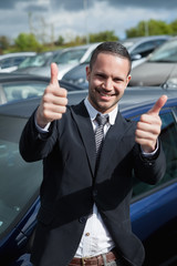 Businessman raising his thumbs while smiling