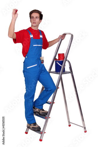 Painter on a stepladder and holding a stamp