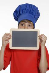 Niño chef sujetando pizarrón de escuela,cocinero.