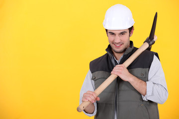 Playful young man holding a pickaxe